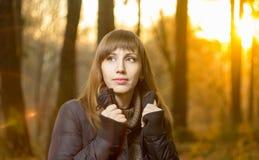年轻美丽的女孩在晚上秋天森林里 免版税库存图片