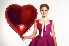 美丽的女孩在晚礼服baloon红色心脏情人节 免版税库存图片