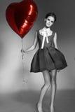 美丽的女孩在晚礼服baloon红色心脏情人节 免版税图库摄影