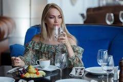 美丽的女孩在有一块玻璃的餐馆在手上 免版税图库摄影