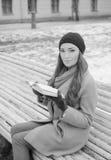美丽的女孩在有书的公园坐长凳,黑白 库存照片