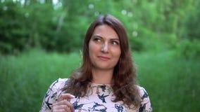 美丽的女孩在有夏天晴朗的天气的森林里站立 影视素材