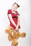 美丽的女孩在有拿着玩具熊的白色圆点的一件红色礼服穿戴了 库存图片