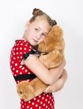 美丽的女孩在有拿着玩具熊的白色圆点的一件红色礼服穿戴了 免版税库存照片