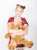 美丽的女孩在有拿着玩具熊的白色圆点的一件红色礼服穿戴了 免版税图库摄影