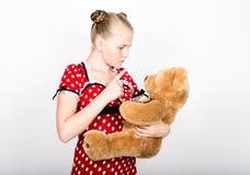 美丽的女孩在有拿着玩具熊的白色圆点的一件红色礼服穿戴了 免版税库存图片