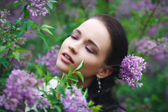 美丽的女孩在有花树的一个公园 免版税库存图片