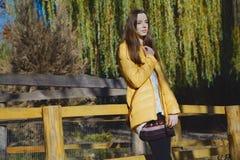 年轻美丽的女孩在木篱芭附近站立在城市动物园里 免版税库存图片