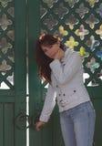 美丽的女孩在木门附近的白色夹克的 免版税库存图片