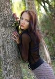 美丽的女孩在树附近站立 免版税库存照片