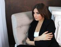 美丽的女孩在椅子坐并且拥抱她的胳膊 免版税库存图片