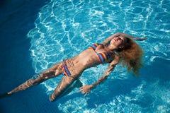 美丽的女孩在池浮动 免版税库存图片