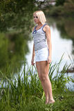 年轻美丽的女孩在河的夏天 免版税库存图片