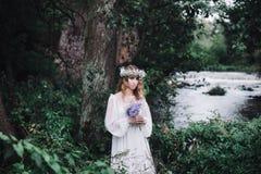 美丽的女孩在河附近的一个黑暗的森林里 库存照片