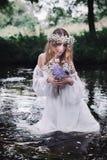 美丽的女孩在河附近的一个黑暗的森林里 免版税图库摄影