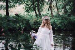 美丽的女孩在河附近的一个黑暗的森林里 免版税库存照片