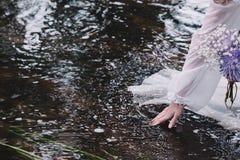 美丽的女孩在河附近的一个黑暗的森林里 库存图片