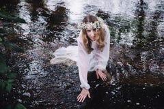 美丽的女孩在河附近的一个黑暗的森林里 免版税库存图片