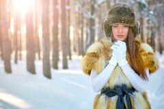 美丽的女孩在温暖的衣裳的冬天森林里 图库摄影