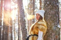 美丽的女孩在温暖的衣裳的冬天森林里 库存图片
