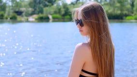 年轻美丽的女孩在湖岸站立 股票视频