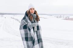 美丽的女孩在用有热水瓶杯子的格子花呢披肩包括的冬天 库存照片