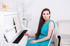 美丽的女孩在白色钢琴附近坐并且凝视 免版税库存图片