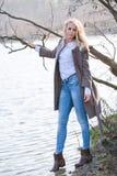 年轻美丽的女孩在秋天河站立 免版税库存照片