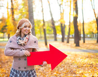 美丽的女孩在秋天的指向一个方向 免版税库存照片