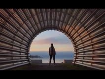 美丽的女孩在管子线的曲拱站立 免版税库存照片