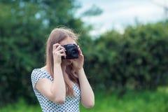 年轻美丽的女孩在老葡萄酒照相机拍摄了 图库摄影