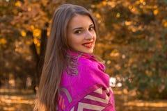 美丽的女孩在肩膀的一条大温暖的围巾站立斜向一边并且微笑 库存照片