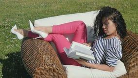 美丽的女孩在自然读了在柳条扶手椅子的书 股票录像