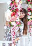 年轻美丽的女孩在花中掩藏 免版税库存图片