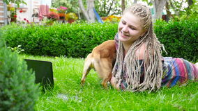 美丽的女孩在草和戏剧说谎与狗 HD 股票视频