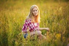 美丽的女孩在草坐 库存照片