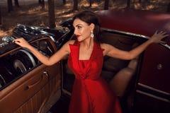 美丽的女孩在葡萄酒汽车前面站立 库存照片