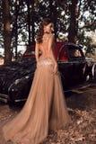 美丽的女孩在葡萄酒汽车前面站立 免版税库存图片