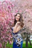 美丽的女孩在豪华的春天庭院里站立 免版税库存照片