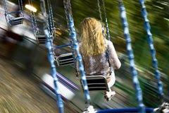 年轻美丽的女孩在链子暂停的摇摆乘坐 库存照片