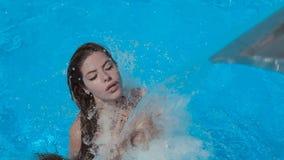 美丽的女孩在飞溅,游泳并且获得乐趣 股票视频