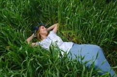 美丽的女孩在麦子的绿色耳朵的中领域在 免版税库存照片