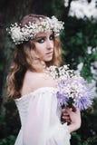 美丽的女孩在黑暗的森林里 免版税图库摄影