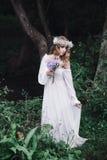 美丽的女孩在黑暗的森林里 库存图片