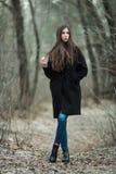 年轻美丽的女孩在黑外套蓝色围巾探索的秋天/春天森林公园 有华美的extr的一个典雅的深色的女孩 免版税库存图片