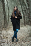 年轻美丽的女孩在黑外套蓝色围巾探索的秋天/春天森林公园 有华美的extr的一个典雅的深色的女孩 免版税图库摄影