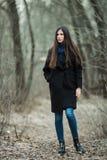 年轻美丽的女孩在黑外套蓝色围巾探索的秋天/春天森林公园 有华美的extr的一个典雅的深色的女孩 免版税库存照片