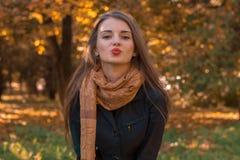美丽的女孩在直接地看一条长的围巾的秋天公园站立并且送亲吻 库存照片