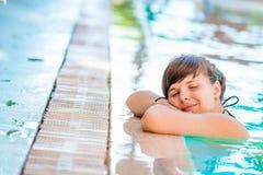 美丽的女孩在水池放松 库存图片