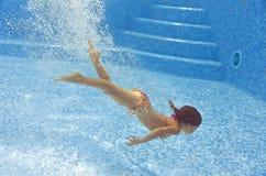 美丽的女孩在水池潜水并且游泳在水面下 免版税库存图片